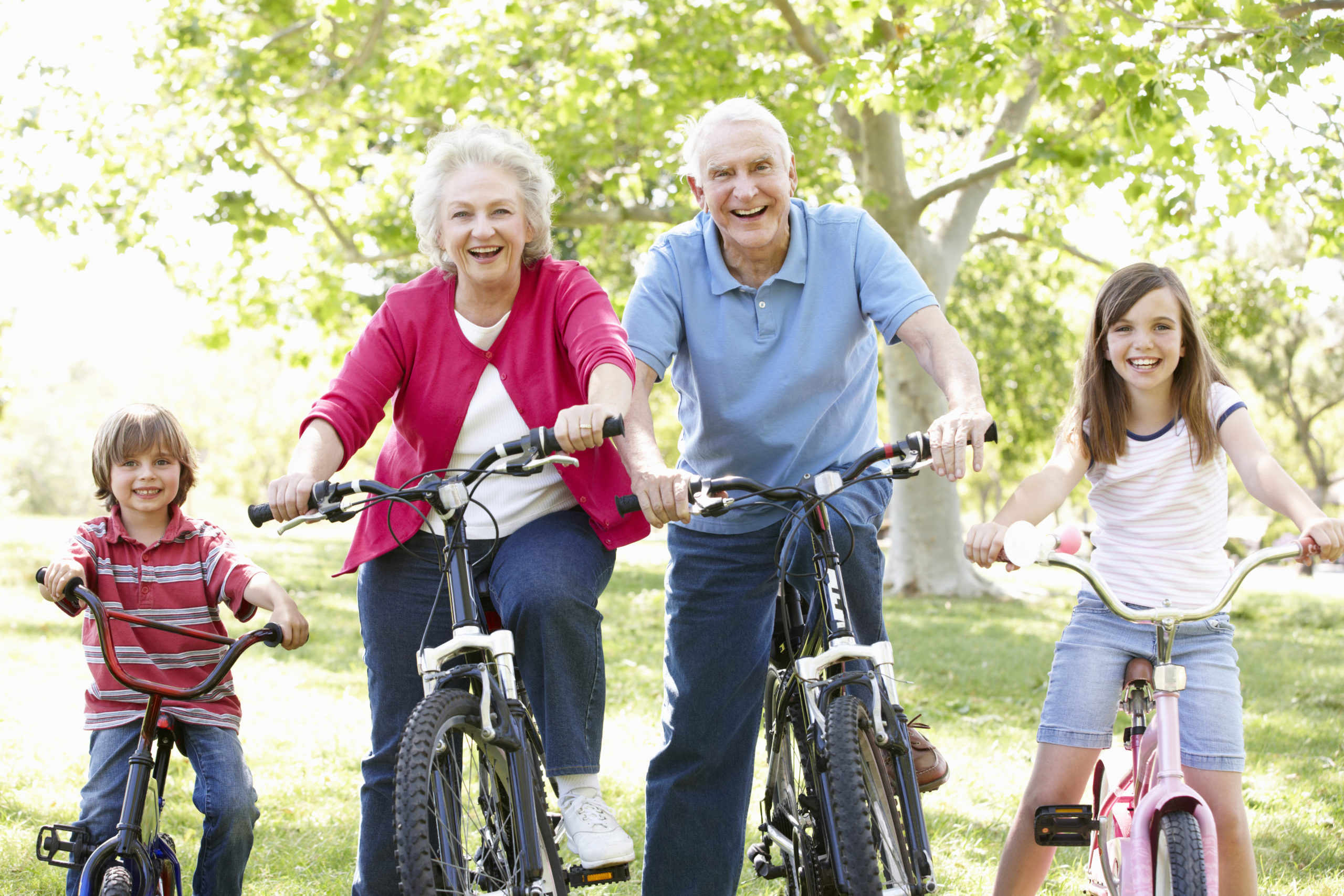 Senior couple with grandchildren on bikes smiling at camera